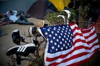 A migrant rested Wednesday near a U.S. flag and some shoes drying in the sun at a sports complex  in Tijuana, across the border from San Diego, Calif. Thousands of migrants are waiting there to apply for asylum in the United States.(Ramon Espinosa/The Associated Press)