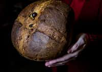 Employee Mila Alvarado holds a panettone at Jimmy's Food Store.(Carly Geraci/Staff Photographer)