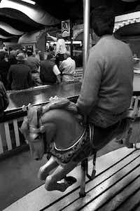 Tom Kuhn of Oakland, Md., sat on one of the merry-go-round horses inside Penny Whistle Park in Dallas as auctioneers from Norton Auctioneers of Michigan took bids for the amusement park concessions and rides in 1995.