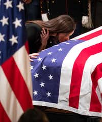 Barbara Pierce Bush kisses the flag-draped casket of her grandfather President George H.W. Bush as he lies in the Rotunda of the U.S. Capitol on Tuesday, Dec. 4, 2018, in Washington.(Smiley N. Pool/Staff Photographer)