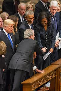 Former President George W. Bush, hands something to a laughing Michelle Obama as (from left) President Donald Trump, first lady Melania Trump, former President Barack Obama, former President Bill Clinton and former Secretary of State Hillary Clinton, look on before Bush took his seat for the State Funeral for George H.W. Bush, the 41st President of the United States, at the Washington National Cathedral on Wednesday, Dec. 5, 2018, in Washington. (Smiley N. Pool/Staff Photographer)