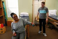 "Samantha Barber lifts weights in a session with physical therapist Blake Withrow at Green Oaks Physical Therapy in DeSoto. ""This is hard,"" Barber, a former bodybuilder, said while working to lift a 1-pound weight. ""It feels like a hundred pounds.""(Ryan Michalesko/Staff Photographer)"