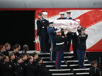 A joint services honor guard carries the flag-draped casket of former President George H.W. Bush from the funeral train pulled by the custom-painted Union Pacific Locomotive 4141 to his final resting place at the George H. W. Bush Presidential Library Center on Texas A&M University campus in College Station, Texas on Thursday, Dec. 6, 2018. (Rose Baca/The Dallas Morning News)
