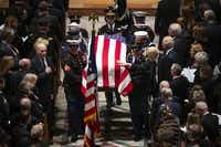 Former Sen. Alan Simpson reaches out to touch the flag-draped casket as a military honor guard carries departs the Washington National Cathedral at the conclusion of the State Funeral for George H.W. Bush, the 41st President of the United States, on Wednesday, Dec. 5, 2018, in Washington. (Smiley N. Pool/The Dallas Morning News)