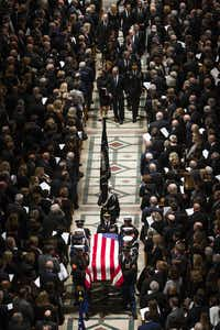 The Bush family, lead by former President George W. Bush and Laura Bush, follows behind as a military honor guard carries the flag-draped casket as it depart the Washington National Cathedral at the conclusion of the State Funeral for George H.W. Bush, the 41st President of the United States, on Wednesday, Dec. 5, 2018, in Washington. (Smiley N. Pool/The Dallas Morning News)