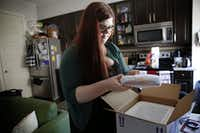 Hannah Wise opens up a delivery containing her medicine at her home in Dallas on April 27, 2016. (Rose Baca/The Dallas Morning News)(Rose Baca/Staff Photographer)