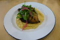 The yardbird and grits at Bonton Farms Cafe includes a charbroiled hind chicken quarter nested on top of rustic Anson Mills grits and garnished with arugula and pickled onions.(Kim Pierce/Special Contributor)