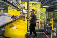 Elizabeth Moran picks up a package from a robot-delivered pod at an Amazon fulfillment center in Coppell.(Shaban Athuman/Staff Photographer)