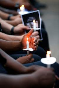 Dallas police officers hold candles during a candlelight vigil for one of their own in this photo from earlier this summer.<div><br></div>(Jae S. Lee/Staff Photographer)