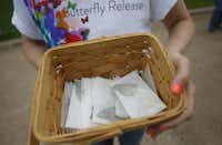 In this file photo, volunteer Christina Decker of Faith Presbyterian Hospice hands out butterflies to be released as part of a service to remember loved ones who have died. (Anja Schlein/Special Contributor)