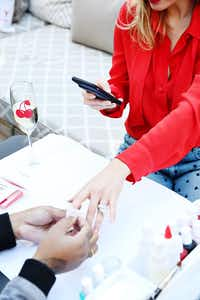 A woman on her phone gets a manicure from a Cherry nail technician.(Courtesy of Cherry/Courtesy of Cherry)