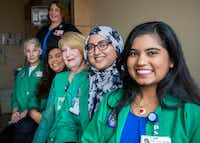 <p>Nurse manager Cyndi Kelley (standing)relies on volunteers including (from left) Danna Orr, Aly Rodrigues, Beverley Denman, Aniqa Arephin and Akanksha Devasigamani to hold infants and help with daily tasks.</p>(Carly Geraci/Staff Photographer)