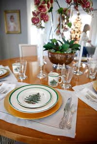"""<p><span style=""""font-size: 1em; background-color: transparent;"""">LIke her mother and grandmother before her, Meredith Land, with help from daughter McCall, sets her table in December with Spode's Christmas Tree dishes.</span></p>(Tom Fox/Staff Photographer)"""