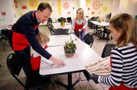 Meredith Land, husband Xan and children Alexander and McCall help set the table for lunch at the Salvation Army's Carr P. Collins Social Service Center on Harry Hines.(Tom Fox/Staff Photographer)