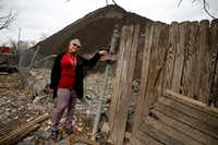 Homeowner Marsha Jackson looks over her damaged fence at the large mounds of shredded roofing shingles that Dallas City Hall now says are getting into the Five Mile Creek tributary.(Tom Fox/Staff Photographer)