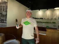 Lee Theilen turned his pickling hobby into a new artisan business, Pickletopia, which just had its soft opening. That's a full sour pickle he's holding. (Kim Pierce/Special Contributor)