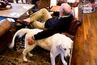 Glen Carter pets his dog, Ace,  as he talks to his wife, Janet, in their University Park home.(Shaban Athuman/Staff Photographer)