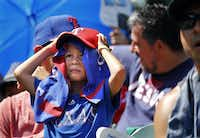Young Texas Rangers fan Ripken Echols takes cover from the searing sun as he watches his team face the Cleveland Indians at Globe Life Park in Arlington, Texas, Sunday, July 22. By the end of the game the temperature was 108¼, one of the hottest games on record. The Rangers won, 5-0.(Tom Fox/Staff Photographer)