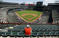 A lone baseball fan, who wished not to provide his name, had several sections of seats in the sun to choose from during the Texas Rangers-Cleveland Indians game at Globe Life Park in Arlington, Texas, Sunday, July 22. By the end of the game, the temperature was 108¼, one of the hottest games on record.(Tom Fox/Staff Photographer)