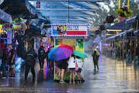 Julie Fernandez, Catalina Fernandez, and Kariss Fernandez, 10, buy game cards in the rain in the midway at the State Fair of Texas on Tuesday, October 9 at Fair Park in Dallas.(Ashley Landis/Staff Photographer)