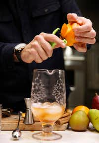 Alex Fletcher, beverage director of the Dog and Pony Show Texas peels an orange for a Cinnamon Pear Old-Fashioned(Vernon Bryant/Staff Photographer)