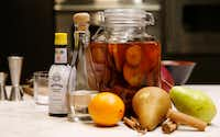 Bitters, simple syrup, orange and bourbon infused with cinnamon and pears for use in a Cinnamon Pear Old-Fashioned(Vernon Bryant/Staff Photographer)