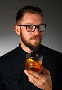 Alex Fletcher, beverage director of the Dog and Pony Show TX, holds up a Cinnamon Pear Old-Fashioned with infused bourbon(Vernon Bryant/Staff Photographer)