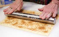 After getting brown sugar sprinkled onto puff pastry, use a roller to press in the sugar to the dough in order to make palmiers.(Nathan Hunsinger/Staff Photographer)