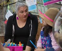 Ofelia Faz-Garza helps her daughter, Paloma Garza, 7, write a letter at the booth she was running at an arts bazaar  at the CocoAndre Chocolatier in Oak Cliff on Nov. 24, 2018. (Daniel Carde/Staff Photographer)