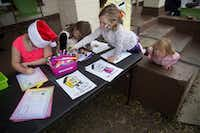 From left, Nova Ayala, 8, writes a letter to Santa Claus as sisters Lucy Shearer, 6, and Ruby Shearer, 5, color while their younger sister, Jolie Shearer, 2, watches.(Daniel Carde/Staff Photographer)