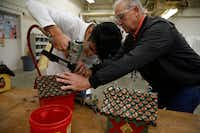Sophomore Servando Badillo works with shop teacher Doug Palmer to affix bottle caps for the roof of his birdhouse during shop class at Skyline High School.(Nathan Hunsinger/Staff Photographer)