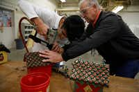 Sophomore Servando Badillo works with shop teacher Doug Palmer to affix bottle caps for the roof of his birdhouse during shop class at Skyline High School.  (Nathan Hunsinger/Staff Photographer)
