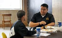 Dallas Police Officer Victor Guardiola (right) talks with Carter High School student Sedric Owens on Dec. 13, 2018, as part of a mentoring program at the school. Guardolia was also mentored by a police officer when he was a teen.(Louis DeLuca/Staff Photographer)