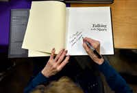 """Bobbie Wygant, 92, signs a copy of her book """"Talking to the Stars"""" to a fan after speaking at the Oak Cliff Lions Club's  weekly luncheon on Dec. 19.<br>(Ben Torres/Special Contributor)"""