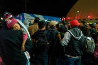 Asylum seekers stand at a bus stop after they were dropped off by Immigration and Customs Enforcement at the Greyhound station in downtown El Paso late on Sunday. The group of around 200, mostly made up of Central Americans, were left without money, food and means of communication. Volunteers from Annunciation House and other local churches came to aid and find a place to house them for the night. (PAUL RATJE/AFP/Getty Images)