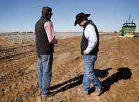 Matt Farmer (right) talks with his son-in-law Garron Morgan while workers harvest their cotton in Lynn County south of Lubbock.(Rose Baca/Staff Photographer)