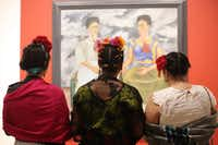 "Three Frida Kahlo lookalikes stand in front of the artist's 1939 work, 'The Two Fridas,' at the Dallas Museum of Art during the exhibit ""Mexico 1900-1950: Diego Rivera, Frida Kahlo, Jose Clemente Orozco and the Avant-Garde."" (Gregory Castillo/Photo: Gregory Castillo)"