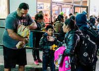 A local man hands out hamburgers to Central American migrants waiting outside the Greyhound Station in El Paso after they were dropped off by Immigration and Customs Enforcement in downtown El Paso late on December 23.(PAUL RATJE/AFP/Getty Images)