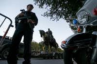 A Dallas Police officer secures an area as a truck carries the Robert E. Lee statue at Robert E. Lee Park on Turtle Creek Boulevard in 2017(Jae S. Lee/Staff Photographer)