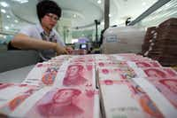 A teller counts yuan banknotes in a bank in Lianyungang, east China's Jiangsu province on August 11, 2015. ( /AFP/Getty Images)