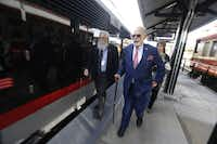 Grapevine Mayor William D. Tate (right) walks with Paul McCallum, executive director of the Grapevine Convention and Visitors Bureau, before boarding the Trinity Metro TEXRail train Monday in Grapevine for its maiden trip from the Grapevine/Main Street Station to DFW Airport.(Nathan Hunsinger/Staff Photographer)