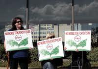 Dallas residents Stacy Hoover-Bell (left), Jeri Huber and Carol Considine gather outside Dallas City Hall to protest Oncor's trimming of trees in the Lakewood and Oak Cliff neighborhoods in Dallas on Nov. 10, 2010. Governments respond much more readily to coalitions than to a larger population who care about affordable housing.(File Photo/Staff)
