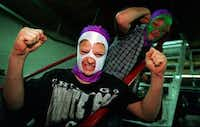 """Oak Cliff wrestling fans John """"Smokey"""" Buford and his  friend Willie """"Tag"""" Page, both 13, put on the wrestling masks they'd just bought at a souvenir stand before watching a regular Friday night show at the Sportatorium in 1996.(1996 File Photo/Staff)"""