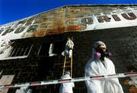 Pedro Enriquez (right) and other workers from L.A. Environmental Inc. stripped asbestos-laden shingles from the exterior of the Sportatorium to prepare it for demolition in 2003.(2003 File Photo/Staff)