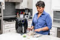 Urvashi Pitre prepares tandoori shrimp in an air fryer at her home in Keller.(Shaban Athuman/Staff Photographer)