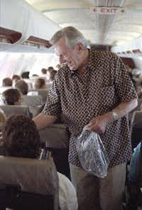 Southwest Airlines chief Herb Kelleher passes out peanuts to customers on a flight from Dallas to San Antonio.(File Photo/Staff)