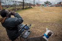 "Charlie Alexander Jr., who is homeless, took a sip of beer on Dec. 12 while his dog King sat by his side on the lot where the future Vickery Meadow library will be built. Alexander picks up the trash that is littered on the lot daily.  ""Since I am out here I thought, 'Hell ,I will give back,'"" he said.(Carly Geraci/Staff Photographer)"