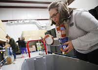 Volunteer Michelle McLemore organizes donated food items before assembling meals for qualifying children at Frisco Fastpacs headquarters.(Rose Baca/Staff Photographer)