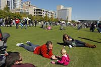 Matt Baker lies on the grass as he plays with his 11-month-old daughter, Kate Baker, at Klyde Warren Park(File Photo/Staff)