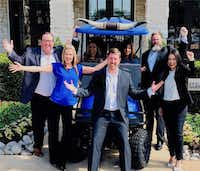 Valiant Residential's leadership team and onsite staff gather around CEO Craig Lashley. The property management company has a fleet of Texas longhorn golf carts to add a little fun to the job. (Valiant Residential)